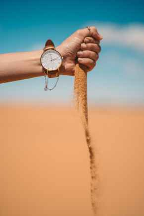 person holding brown rope with silver round analog watch